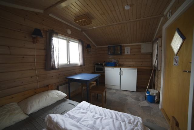 Bilde av ei seng, spiseplasser og kjøkkenkrok